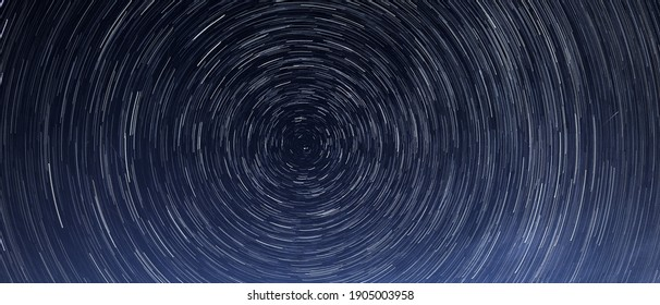 Stellar trails, the rotation of bright stars at night around the Polar Star against a blue sky and a meteor