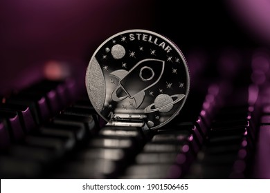 Stellar XLM Cryptocurrency physical coin placed on computer keyboard and lit with purple light.