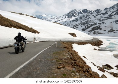 Stelvio Pass, Italy - June 1, 2015 Bikers are traveling through the Stelvio Pass at 2757m asl in a snowy road
