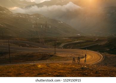 The Stelvio Pass Three biker riding together uphill. Orange sunset light in background. Italy, Passo dello Stelvio