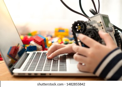 STEM Education - hands of preteen / teenage kid assemble and program his robot on computer laptop for school project. Science Technology Engineering Math. Programming, Robotic, Future learning.