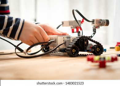 STEM Education, Hands of preteen / teenage kid assemble, learn to program and test his robot for school project. Science Technology Engineering Math. Programming, Robotic Technology, Future learning.