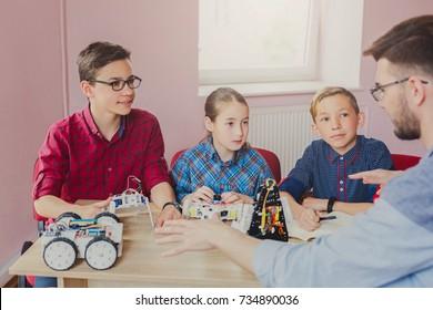 Stem education. Kids creating robots with teacher. Early development, diy, innovation, modern technology concept