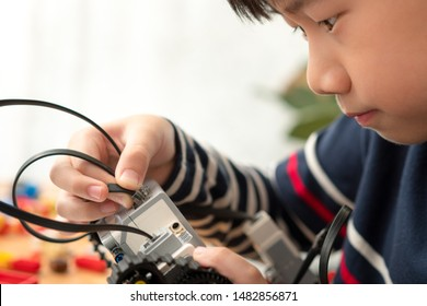 STEM Education - Smart looking preteen / teenage Asian boy assembles Lego Mindstorms EV3 for school project with focus and concentration. Science Technology Engineering Math. Future learning, Closeup.