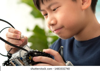 STEM Education - Smart looking preteen / teenage Asian boy assemble cable to his robot with curiosity and passion. Science Technology Engineering Math. Programming, Robotic Technology, Sci-Tech.