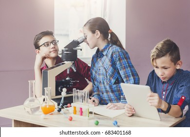 Stem education. Teenagers making chemical experiment in laboratory with reagents and microscope. Early development concept