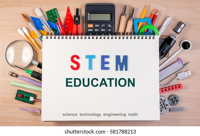 STEM education text on notebook over school supplies or office supplies on school table. Background with school or office material with copy space for text.