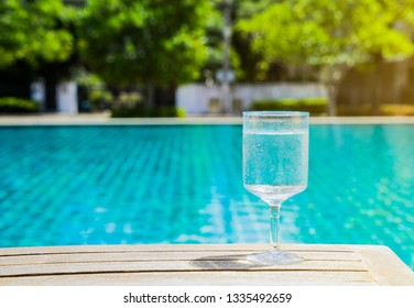 Stem glass of clean and clear still mineral drinking water on wooden table on swimming pool edge, hotel or clubhouse on late morning of summer. Health, dehydrate, sport and vacation travel background