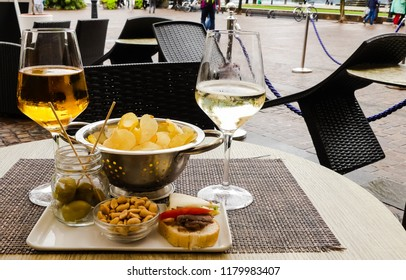 Stem glasses of wine and golden beer, with plate of hors d'oeuvres of olives, peanuts, bruschetta accompanied by colander of crisps. Public square, Riva del Garda, Italy