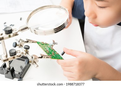 STEM skills in 21st Century Education concept. Young smart Asian elementary school kid work on assemble DIY electronic project on PCB circuit board with resistors, capacitors and potentiometer.
