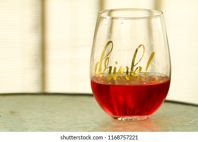 """Stemless glass filled with Cabernet Franc Rose and in gold letters """"drink"""" in front of a blurry glass table and patio screen."""