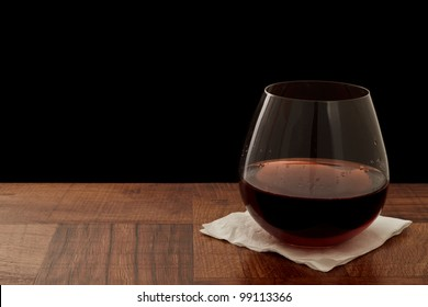 stemless glass of red wine on a bar top isolated on a black background