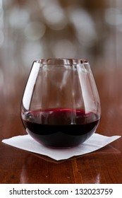 stemless glass with red wine served on a bar