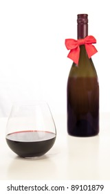 stemless glass of wine on a white table with an out of focus bottle of whine with a ribbon