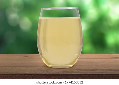 Stemless wineglass filled with white wine atop a rustic brown wood tabletop with a soft nature background
