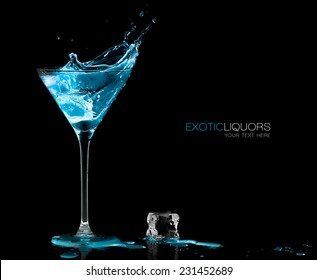 Stemmed cocktail glass with blue alcoholic drink splashing out, close-up isolated on black. Template design with sample text