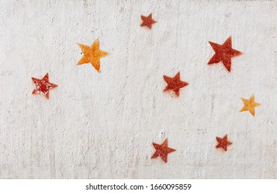 Stencil graffiti, red and yellow stars on a concrete wall