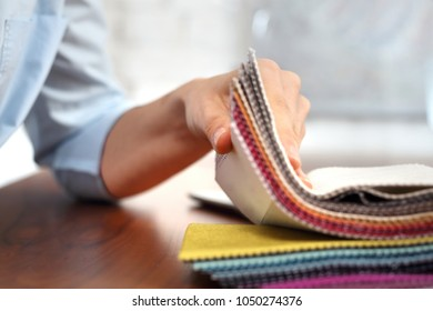 Stencil for upholstery fabrics. The woman watches the colors and patterns of upholstery fabrics.
