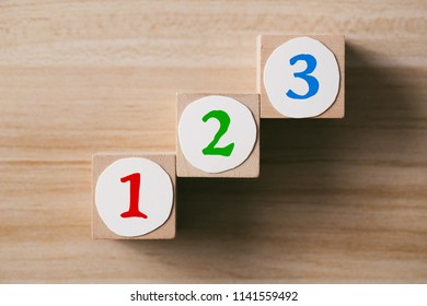 Step by step concept on the wooden desk background. The steps to success.