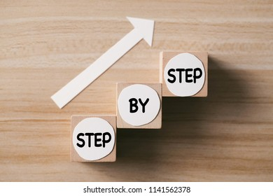 Step by step concept on the wooden desk background. Steps to success.