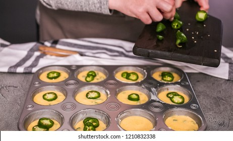 Step by step. Filling metal muffin pan with cornbread batter to bake spicy jalapeno cornbread muffins.