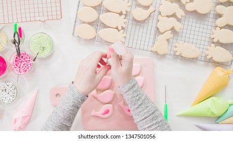 Step by step. Flat lay. Decorating Easter sugar cookies with rotal icing.