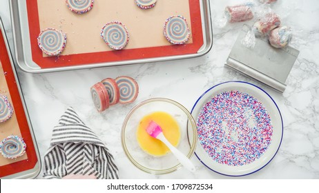 Step by step. Flat lay. Rolling edges of red, white, and blue pinwheel sugar cookies in sprinkles.