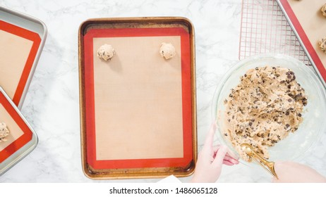 Step by step. Flat lay. Scooping homemade chocolate chip cookies with metal dough scoop to the baking sheet.