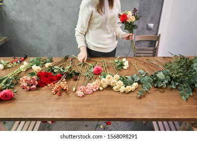 Step by step florist woman creates red beautiful bouquet of mixed flowers. Handsome fresh bunch. Education, master class and floristry courses. Flowers delivery. European floral shop concept.