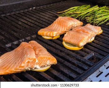 Step by step. Grilling salmon with lemons on outdooor gas grill.