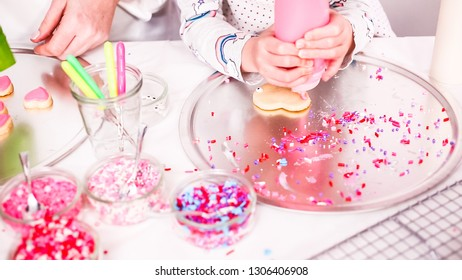 Step by step. Little girl decarting sugar cookies with royal icing and sprinkles for Valentine's Day.