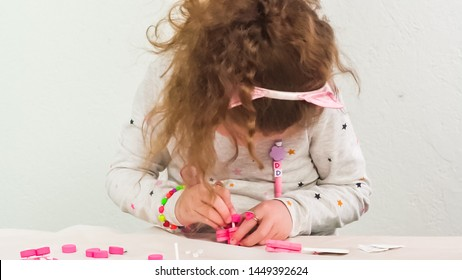 Step by step. Little girl making unicorn craft out of white and pink paper foam.