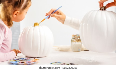 Step by step. Mother and daughter decorating Halloween craft pumpkin with unicorn theme.