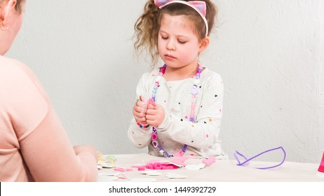 Step by step. Mother and daughter making unicorn craft from paper foam.