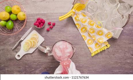 Step by step. Preparing raspberry lemonade with fresh lemons and raspberries in drinking mason jars.