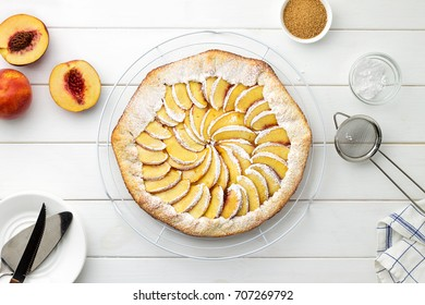 Step by step recipe galette with nectarines. Fresh baked open pie with nectarines on wire stand on white wooden background. Top view.