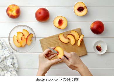Step by step recipe galette or pie with nectarines. Female hands lay out slices of nectarine on the dough. Baking process top view.