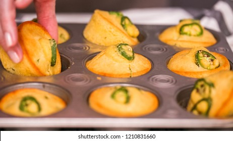 Step by step. Taking out freshly baked spicy jalapeno cornbread muffins from metal muffin pan.