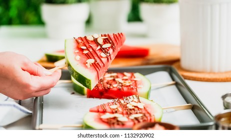 Step by step. Watermelon wedges garnished with chocolate and sea salt  on the stick on baking sheet.