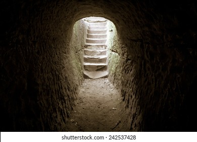 Step Into The Light. Dark stone hallway with a upward staircase leading into the sunlight.