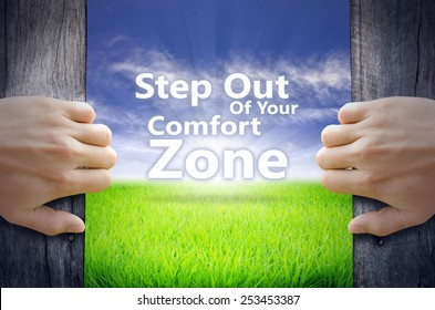 """""""Step out of your comfort zone"""" Motivational quotes. Hands opening a wooden door then found a texts floating among new world as green grass field, Blue sky and the Sunrise."""