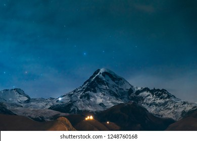 Stepantsminda, Georgia. Natural Real Night Starry Sky With Glowing Stars Over Peak Of Mount Kazbek Covered With Snow. Famous Gergeti Church In Night Lightning. Beautiful Georgian Landscape