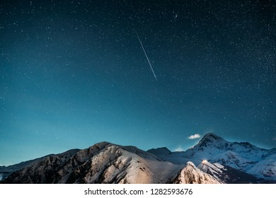 Stepantsminda, Georgia. Natural Winter Night Starry Sky With Glowing Stars And Real Meteoric Track Trail Over Mount Kazbek. Beautiful Night Georgian Landscape With Glowing Stars And Meteorite Trail.