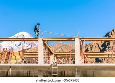 Stepantsminda, GEORGIA, NOVEMBER 11, 2016: Workers on top of the building construction against mountains