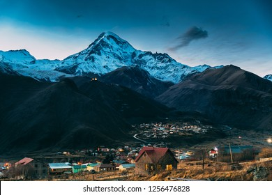 Stepantsminda, Georgia. Peak Of Mount Kazbek Covered With Snow, Famous Gergeti Church And Countryside Houses In Evening Lightning. Beautiful Georgian Landscape