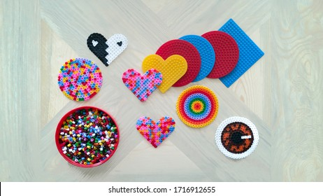 Step-by-step instructions for thermo mosaic: step 1.Set of several circle,square and heart-shaped forms with pins,jar and container lid with beads.Concept of quiet family game with children at home