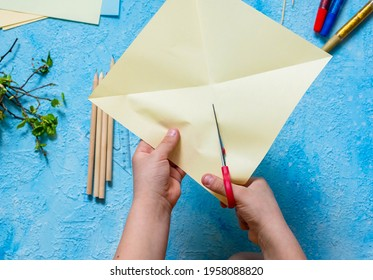 Step-by-step making of a paper weather vane by a child on a blue concrete background. Children's creativity, divas, crafts. Paper crafts