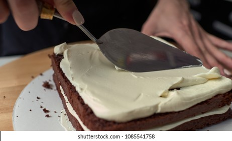 Step-by-step preparation of black designer cake. The confectioner covers the cake with cream.