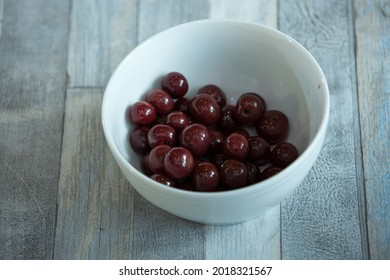 Step-by-step process of making chocolates from dark chocolate and cherries in cognac at home. Cherries in candy brandy are prepared in a plate. Culinary blog concept.