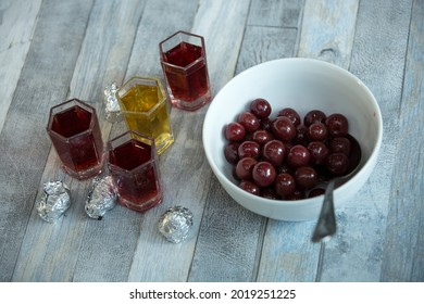 Step-by-step process of making chocolates from dark chocolate and cherries in cognac at home. Ready-made sweets, cherries on brandy in a plate and glasses with brandy on cherries.